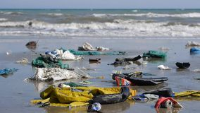 Ciérrese para arriba de la basura y de la basura plásticas en la playa Tiro estático metrajes