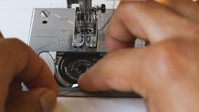 Ciérrese para arriba de la bobina del ajuste de la mano del hombre en dispositivo de la lanzadera de la máquina de coser almacen de video