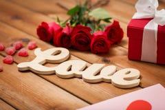 Ciérrese para arriba de la caja de regalo, de rosas rojas y de tarjeta de felicitación Imagen de archivo