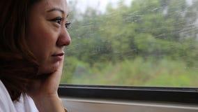 Ciérrese para arriba de la cara de la mujer asiática en un tren, sonriendo en la visión almacen de video