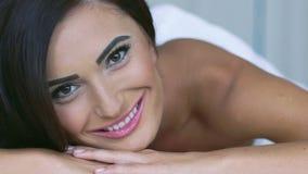 Ciérrese para arriba de la cara de la mujer elegante que sonríe, mirando en cámara en el sofá lentamente metrajes