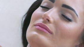 Ciérrese para arriba de la cara de la mujer joven que recibe masaje eléctrico del facial del ultrusound metrajes