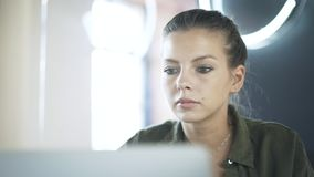 Ciérrese para arriba de la cara de la mujer joven s que trabaja en su ordenador portátil almacen de metraje de vídeo