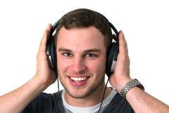Ciérrese para arriba de la cara del hombre joven que escucha la música Imágenes de archivo libres de regalías