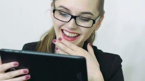 Ciérrese para arriba de la cara femenina que mira la pantalla de la tableta digital metrajes