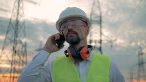 Ciérrese para arriba de la cara de un ingeniero de sexo masculino mientras que habla en un teléfono cerca de líneas eléctricas metrajes