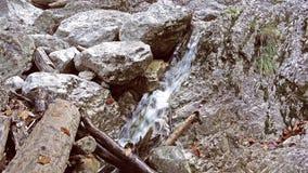 Ciérrese para arriba de la cascada, agua que cae sobre las piedras en la cámara lenta, corrientes que caen sobre rocas, salpica,  metrajes