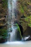Ciérrese para arriba de la cascada de la cascada sobre la roca cubierta de musgo Fotografía de archivo libre de regalías