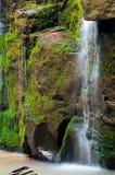 Ciérrese para arriba de la cascada de la cascada sobre la roca cubierta de musgo Fotos de archivo