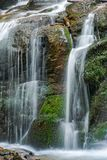 Ciérrese para arriba de la cascada de la cascada sobre la roca cubierta de musgo Foto de archivo
