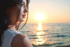 Ciérrese para arriba de la chica joven hermosa que mira en puesta del sol maravillosa del mar fotografía de archivo