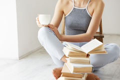 Ciérrese para arriba de la chica joven que sostiene la taza del libro de café que se sienta en piso con los libros sobre la pared Foto de archivo libre de regalías