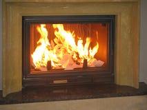 Ciérrese para arriba de la chimenea ardiente en casa Foto de archivo libre de regalías