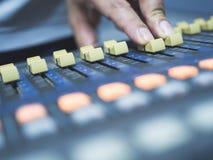 Ciérrese para arriba de la consola de mezcla digital del ajuste de la mano para el estudio de grabación fotografía de archivo