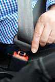 Ciérrese para arriba de la correa de Person In Car Fastening Seat Foto de archivo