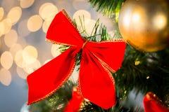 Ciérrese para arriba de la decoración roja del arco en el árbol de navidad Imágenes de archivo libres de regalías