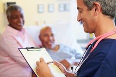 Ciérrese para arriba de la enfermera de sexo masculino Updating Patient Notes Foto de archivo