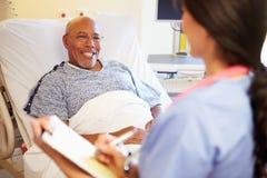 Ciérrese para arriba de la enfermera Updating Patient Notes Fotografía de archivo libre de regalías