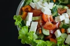 Ciérrese para arriba de la ensalada estupenda orgánica fresca de la comida en el cuenco blanco que se sienta en la tabla de mader Fotografía de archivo