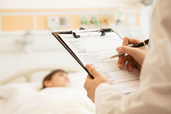 Ciérrese para arriba de la escritura del doctor en una carta médica con el paciente que miente en una cama de hospital en el fondo Foto de archivo