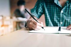 Ciérrese para arriba de la escritura de la mano del estudiante en el papel con un lápiz en clase Fotos de archivo libres de regalías