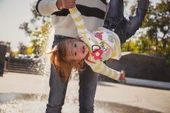 Ciérrese para arriba de la familia cariñosa alegre feliz, madre y la pequeña hija que juega en parque al lado de la fuente, madre fotos de archivo libres de regalías