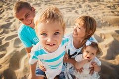 Ciérrese para arriba de la familia cariñosa feliz joven con los pequeños niños en el centro, divirtiéndose en la playa junto cerc fotografía de archivo libre de regalías