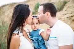 Ciérrese para arriba de la familia joven en las camisetas blancas con una pequeña hija en el vestido que abraza y que se besa, al fotografía de archivo libre de regalías