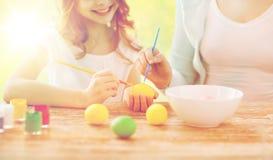 Ciérrese para arriba de la familia que colorea los huevos de Pascua Fotografía de archivo libre de regalías