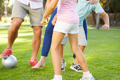 Ciérrese para arriba de la familia que juega al fútbol en parque junto Imágenes de archivo libres de regalías