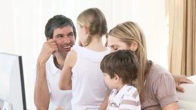 Ciérrese para arriba de la familia usando un ordenador en casa almacen de video