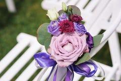 Ciérrese para arriba de la flor adornada en silla de la boda Foto de archivo