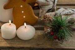 Ciérrese para arriba de la galleta del pan de jengibre con el adornamiento de la forma de la estrella y velas iluminadas Fotos de archivo