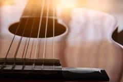 Ciérrese para arriba de la guitarra acústica contra un fondo de madera fotos de archivo