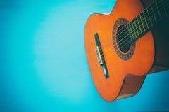 Ciérrese para arriba de la guitarra acústica contra un fondo de madera fotografía de archivo