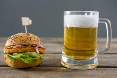 Ciérrese para arriba de la hamburguesa con el vidrio de cerveza Foto de archivo libre de regalías