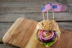 Ciérrese para arriba de la hamburguesa con la bandera americana Fotografía de archivo