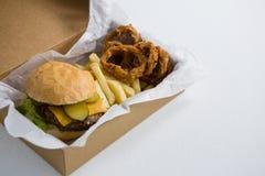 Ciérrese para arriba de la hamburguesa con los anillos de cebolla y las patatas fritas en caja Imagen de archivo