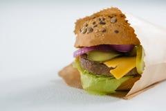 Ciérrese para arriba de la hamburguesa en bolsa de papel Foto de archivo libre de regalías
