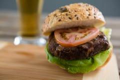 Ciérrese para arriba de la hamburguesa en tabla de cortar Imagen de archivo libre de regalías