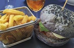 Ciérrese para arriba de la hamburguesa y de fritadas deliciosas en una cesta del metal fotos de archivo