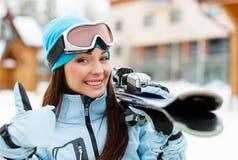Ciérrese para arriba de la hembra que da los esquís que manosea con los dedos para arriba Imágenes de archivo libres de regalías