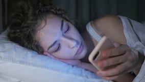 Ciérrese para arriba de la hembra que usa Smartphone en cama en la noche metrajes
