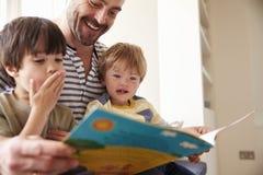 Ciérrese para arriba de la historia de And Sons Reading del padre en casa junto imagen de archivo