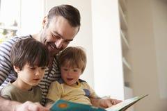 Ciérrese para arriba de la historia de And Sons Reading del padre en casa junto fotografía de archivo