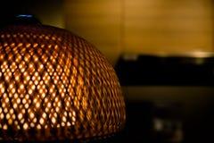 Ciérrese para arriba de la lámpara de bambú tejida lujo con la luz ámbar dentro Pantalla de mimbre a cielo abierto Lámpara vieja  Fotos de archivo