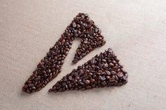Ciérrese para arriba de la letra y incluida en el triángulo hecho de los granos de café imágenes de archivo libres de regalías