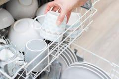 Ciérrese para arriba de la loza del cargamento de la mujer en el lavaplatos Foto de archivo libre de regalías