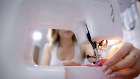Ciérrese para arriba de la máquina de coser plástica moderna en estudio de la adaptación y de la mujer joven en el fondo Proceso  metrajes