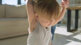 Ciérrese para arriba de la madre joven que enseña a los primeros pasos de la hija metrajes